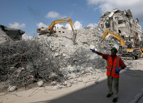 Bulldozers sent by Egypt for Palestinians work at the side of Israeli airstrikes in Gaza